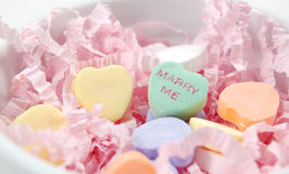 Marry Me Valentine's Hearts. Pile of candy hearts in a white dish with the words Marry Me Stock Photo