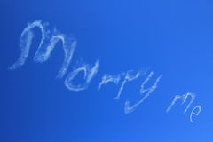 Marry me skywriting in blue sky. MARRY ME skywriting into a clear blue sky through aerobatic maneuver. Low-angle shot Stock Images