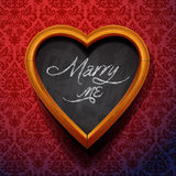 Marry Me written by chalk on heart shaped board Royalty Free Stock Photography
