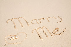 Marry me written on sand Stock Photos