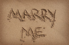 'Marry Me' Written in Sand on Beach Royalty Free Stock Image