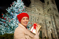 Marry woman with gift box near Christmas tree in Florence, Italy. Marry young woman in white coat showing gift box in front of Christmas tree near Duomo in the stock photos