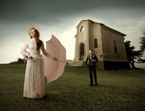Marrying couple. White-dressed woman with umbrella and well-dressed man in front of a church on the background Royalty Free Stock Images