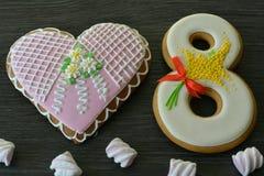 8 mars bonbons pain d'épice et fond en bois gris de table de coeur Image libre de droits