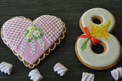 8 mars bonbons pain d'épice et fond en bois gris de table de coeur Photos libres de droits