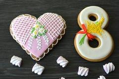 8 mars bonbons pain d'épice et fond en bois gris de table de coeur Images stock