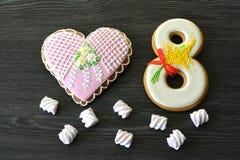 8 mars bonbons pain d'épice et fond en bois gris de table de coeur Image stock