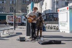 9 mars 2017 Brighton, R-U Jeune jouer d'artiste de rue quitar Image libre de droits