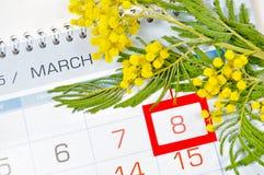 8 mars carte - la mimosa fleurit au-dessus du calendrier avec la date encadrée du 8 mars Images stock