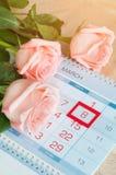 8 mars carte - roses au-dessus du calendrier avec la date encadrée du 8 mars Photos stock