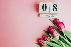 8 mars concept heureux de jour du ` s de femmes Avec le calendrier de bloc en bois et les tulipes roses sur le fond rose Copiez l Photo stock