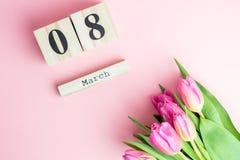 8 mars concept heureux de jour du ` s de femmes Avec le calendrier de bloc en bois et les tulipes roses sur le fond rose Copiez l Image stock