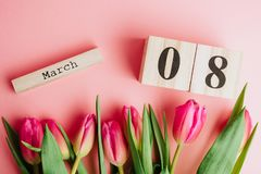 8 mars concept heureux de jour du ` s de femmes Avec le calendrier de bloc en bois et les tulipes roses sur le fond rose Copiez l Photos stock