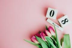 8 mars concept heureux de jour du ` s de femmes Avec le calendrier de bloc en bois et les tulipes roses sur le fond rose Copiez l Photographie stock