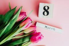 8 mars concept heureux de jour du ` s de femmes Avec le calendrier de bloc en bois et les tulipes roses sur le fond rose Copiez l Images stock