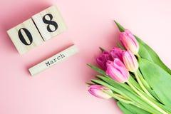 8 mars concept heureux de jour du ` s de femmes Avec le calendrier de bloc en bois et les tulipes roses sur le fond rose Copiez l Photographie stock libre de droits