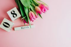 8 mars concept heureux de jour du ` s de femmes Avec le calendrier de bloc en bois et les tulipes roses sur le fond rose Copiez l Photo libre de droits