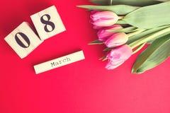 8 mars concept heureux de jour du ` s de femmes Avec le calendrier de bloc en bois et les tulipes roses sur le fond rouge Copiez  Photos stock