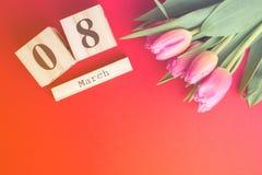 8 mars concept heureux de jour du ` s de femmes Avec le calendrier de bloc en bois et les tulipes roses sur le fond rouge Copiez  Photos libres de droits