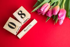 8 mars concept heureux de jour du ` s de femmes Avec le calendrier de bloc en bois et les tulipes roses sur le fond rouge Copiez  Images libres de droits