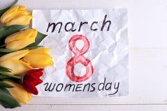 8 mars, et tulipes jaunes et rouges Photographie stock libre de droits