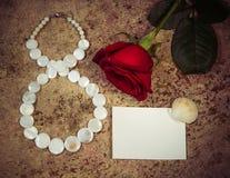 8 mars, fleur de rose de rouge et coquilles Images libres de droits