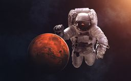 Mars and giant astronaut. Image in 5K resolution for desktop wallpaper. Elements of the image are furnished by NASA Royalty Free Stock Photos