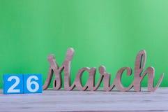 26 mars Jour 26 de mois, calendrier en bois quotidien sur la table et fond vert Printemps, l'espace vide pour le texte Photographie stock