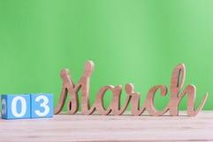 3 mars Jour 3 de mois, calendrier en bois quotidien sur la table et fond vert Printemps, l'espace vide pour le texte Photographie stock