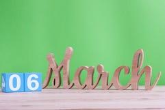 6 mars Jour 6 de mois, calendrier en bois quotidien sur la table et fond vert Printemps, l'espace vide pour le texte Photo stock