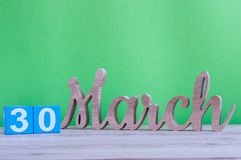 30 mars Jour 30 de mois, calendrier en bois quotidien sur la table et fond vert Printemps, l'espace vide pour le texte Images stock