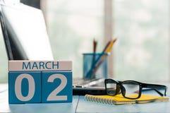 2 mars Jour 2 de mois, calendrier sur le fond de local commercial, lieu de travail avec l'ordinateur portable et verres Printemps Photographie stock
