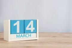 14 mars Jour 14 du mois, calendrier en bois de couleur sur le fond de table Le printemps… a monté des feuilles, fond naturel Comm Image libre de droits