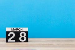 28 mars Jour 28 du mois, calendrier sur la table avec le fond bleu Printemps, l'espace vide pour le texte Images stock