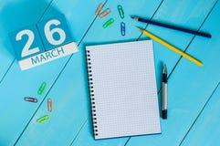 26 mars Jour 26 du mois, calendrier sur le fond en bois bleu de table avec le bloc-notes Printemps, l'espace vide pour le texte Image libre de droits