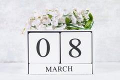 8 mars, jour international du ` s de femmes Calendrier perpétuel en bois et fleurs blanches Image stock