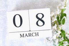 8 mars, jour international du ` s de femmes Calendrier perpétuel en bois et fleurs blanches Photos libres de droits