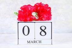 8 mars, jour international du ` s de femmes Calendrier perpétuel en bois et fleurs roses Images stock