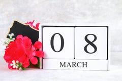 8 mars, jour international du ` s de femmes Calendrier perpétuel en bois, fleurs roses et tableau Copiez l'espace Photos stock