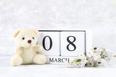 8 mars, jour international du ` s de femmes Un calendrier perpétuel en bois et des fleurs blanches, ours de nounours Images stock