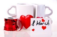 8 mars. Les tasses de café dans la forme de entendent Images stock