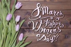 8 mars Lycklig women'sdag! Kort med tulpan på träbackgro Arkivbild