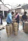 Mars 3, 2017, Matiari, västra Bengal, Indien Köpare som kontrollerar mässingshinkarna, som fabricerades på ett närliggande, shopp Royaltyfria Bilder