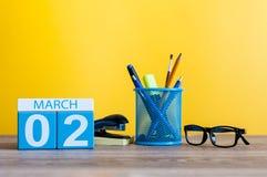 Mars 2nd Dag 2 av marschmånaden, kalender på tabellen med gul bakgrund och kontor eller skolatillförsel Fjädra den tid… ron lämna Arkivfoto
