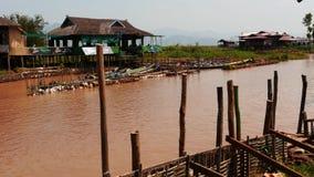 Mars 5 2016 Nyaungshwe, Myanmar brygga med folk och traditionella fartyg i floden - följd för 2 video stock video