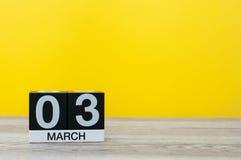 Mars 3rd Dag 3 av månaden, kalender på tabellen med gul bakgrund Vårtid, tömmer utrymme för text Royaltyfri Fotografi