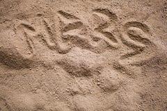 Mars słowo malował na ciemnym piasku z garbkami Fotografia Stock