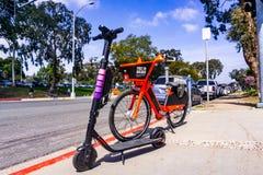 Mars 19, 2019 San Diego/CA/USA - den elektriska cykeln för hoppet som ägdes av Uber och Lyft Escooter, parkerade sidan - vid - si royaltyfri fotografi