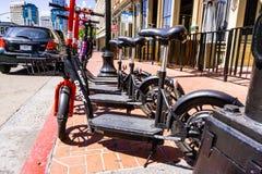 Mars 19, 2019 San Diego/CA/USA - rakknivaktien och Lyft Escooters parkerade sidan - vid - sidan på trottoaren i i stadens centrum royaltyfria foton