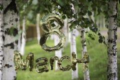 8 mars symbole Le chiffre de huit a fait des boîtes d'or volant au-dessus du fond de bouleau de nature Peut être employé comme gr Photos stock